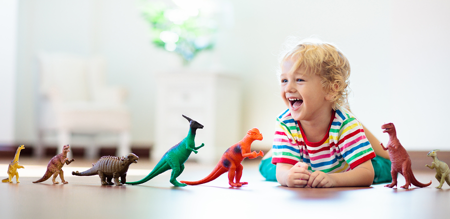 Child Playing With Toy Dinosaurs While Parents Explain Autism to Friends.