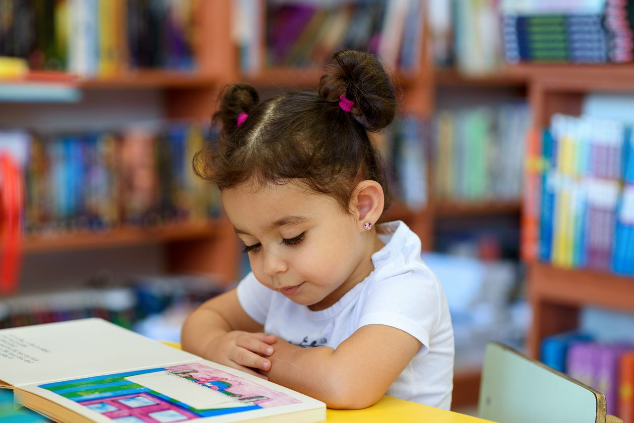 A child reading an adapted book in a special ed classroom.